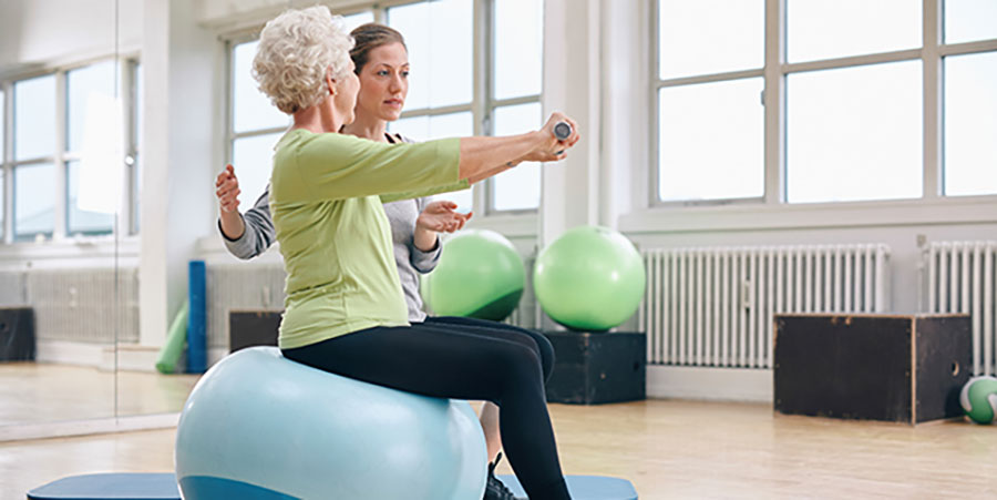 Older woman and trainer lifting weights for rehabilitation in a studio