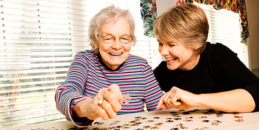 Happy volunteer building a puzzle with an elderly woman