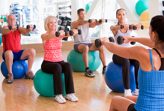 Group of people sitting on exercise balls with weights